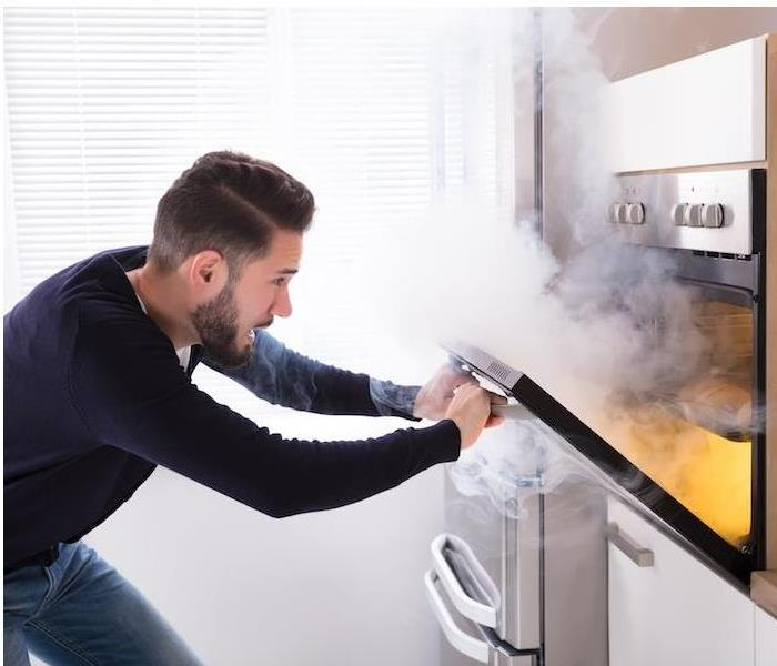 a man with blue shirt opening oven filled with smoke